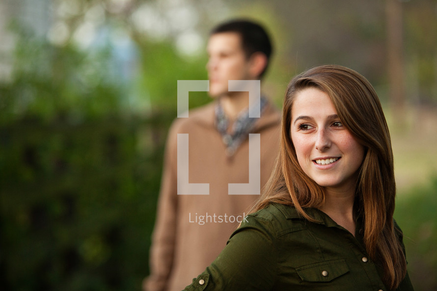 woman smiling in front of a distant man