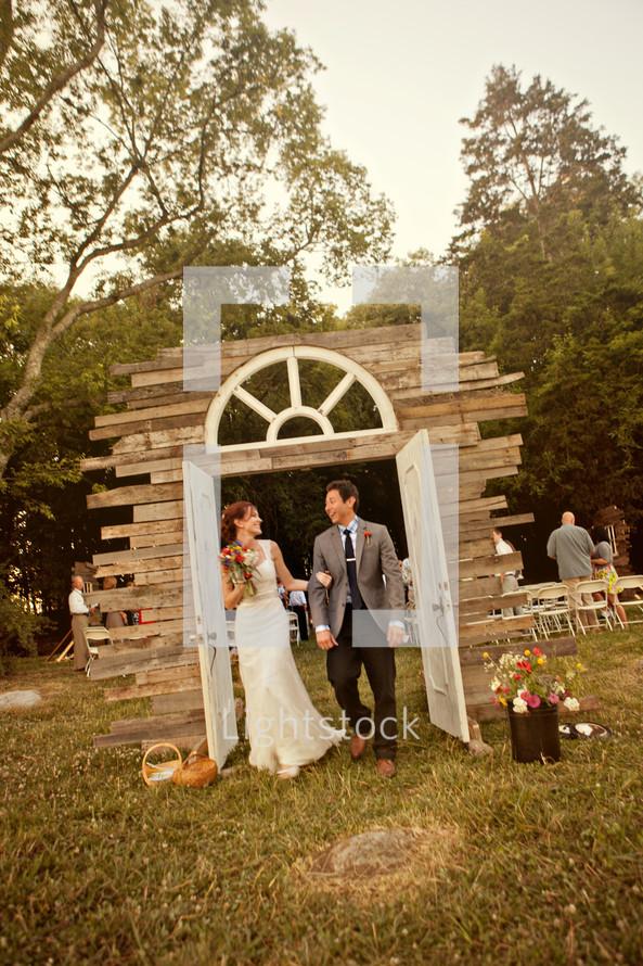 bride and groom walking through doorway arch