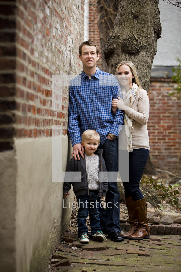 Family standing by a brick wall.