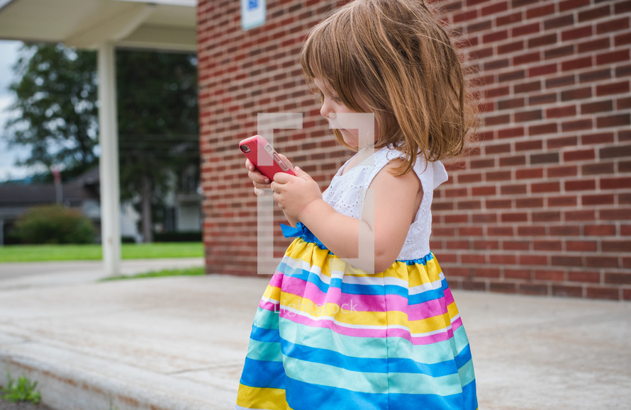 a toddler girl playing with a cellphone