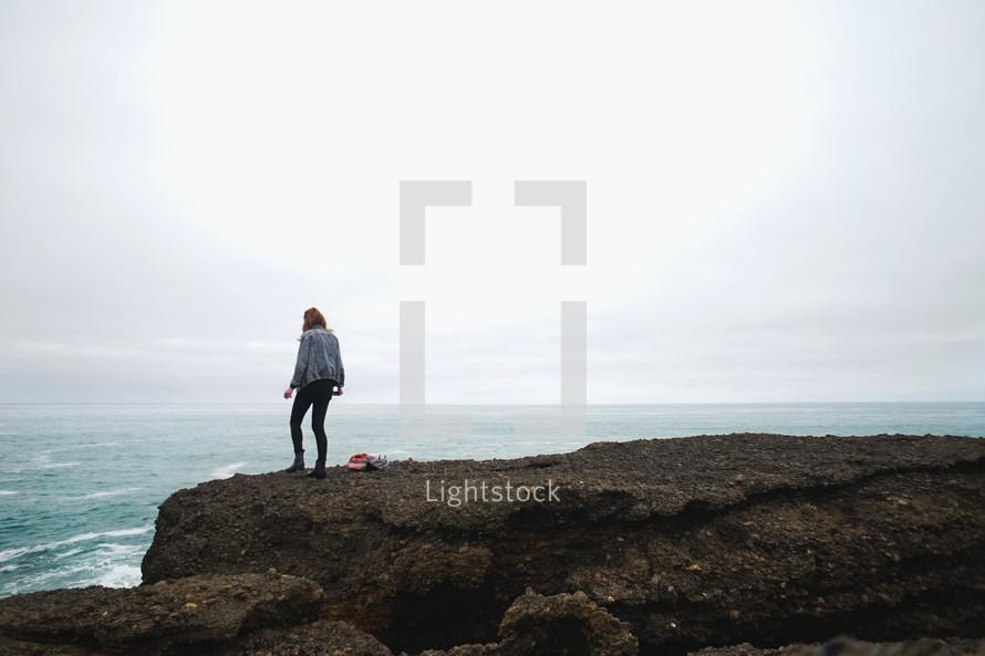 a woman standing on cliffs along a shore
