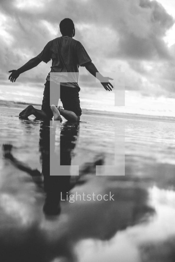 a man kneeling on a beach on wet sand