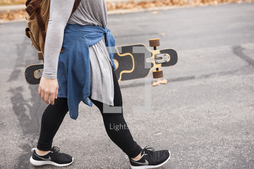 teen girl walking with a skateboard