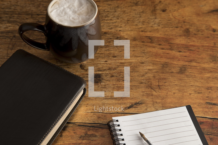 latte, Bible, and notebook on a wooden desk