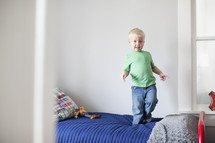 toddler boy jumping on his bed.