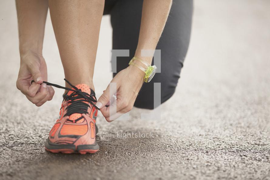 Hands tying a running shoe.