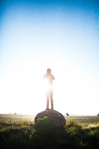Sunshine on a man standing on a round boulder.