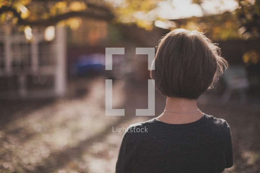 The back of a woman looking out at the yard