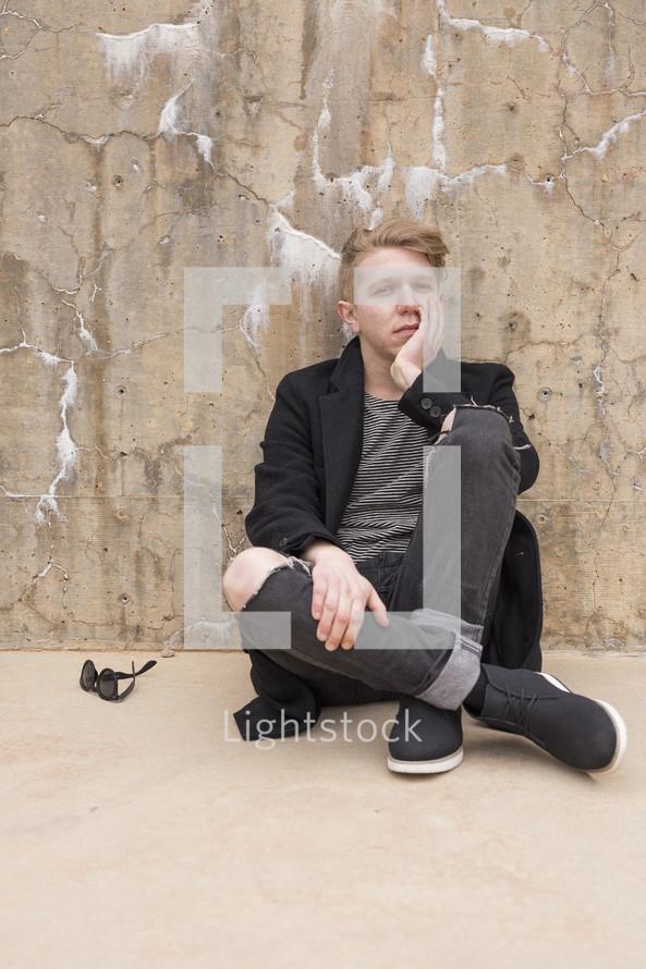 a bored young man sitting on a sidewalk