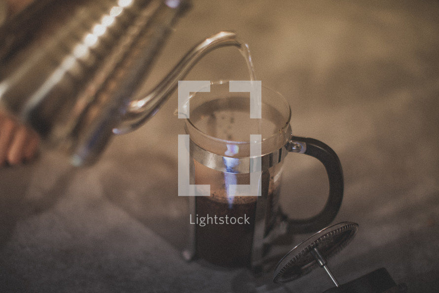 Pouring hot water to brew coffee in a french press