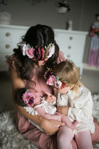 mother holding a swaddled newborn baby and toddler daughter