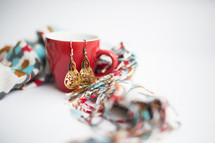 A red cup, a colorful scarf and gold earrings.