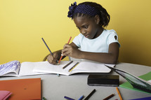 a girl child coloring on paper