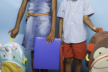 brother and sister holding book bags for the first day of school
