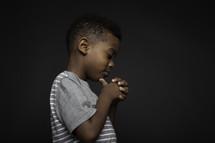 side profile of a boy in prayer