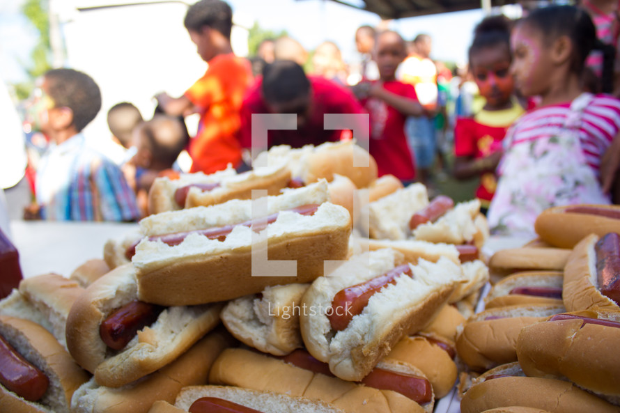 children and a stack of hotdogs