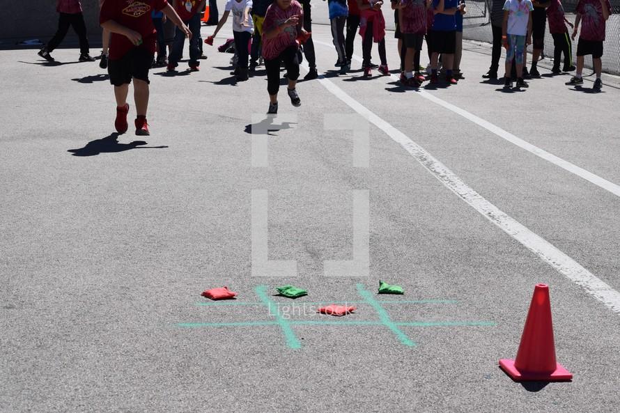 kids playing a bean bag tic-tac-toe race