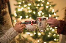 Two women make a toast with their Christmas cups.