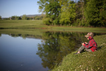 a child sitting at the edge of a pond fishing