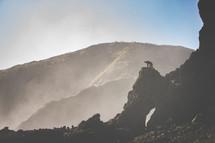 a man kneeling on a rock peak