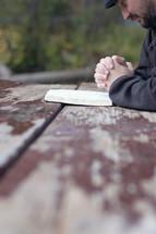 man praying near an open Bible on a picnic table