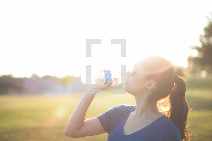 Woman drinking from a water bottle outside.