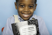 a smiling boy child holding a composition notebook