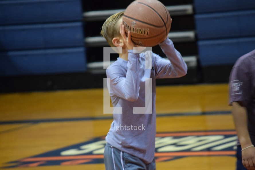 a child shooting a basketball