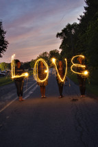 "Four women spelling ""love"" with sparklers."
