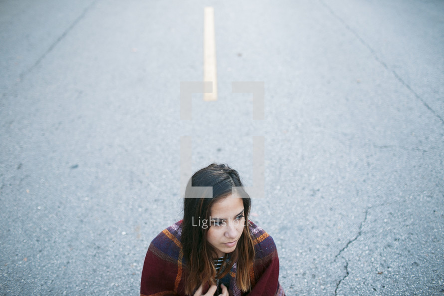 a woman standing in the middle of a road