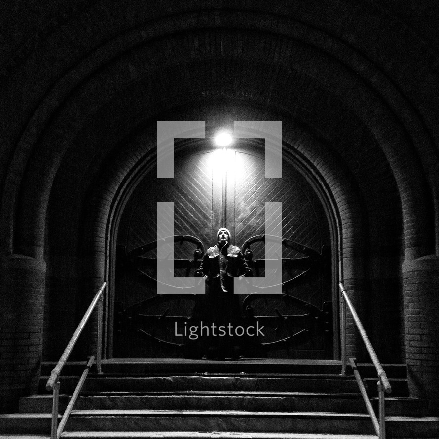 Man on church front steps, underneath light