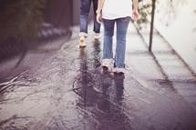 People walking barefoot through puddles on the sidewalk