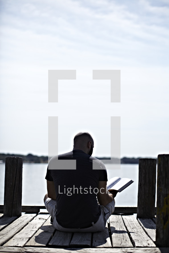 Man sitting on dock reading the Bible