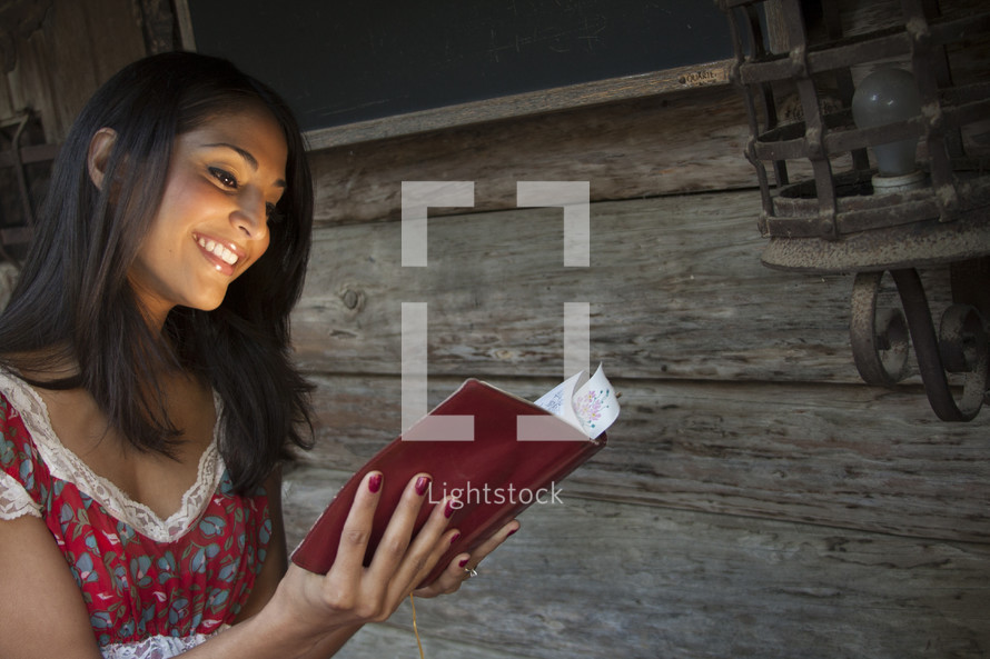 Woman reading bible and smiling