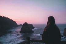 a woman watching the ocean at sunset