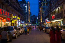 pedestrians and parked cars on a street at night in China