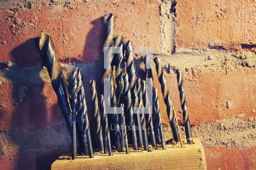Drill bits in a block of wood against a brick wall.