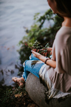 teen girl sitting by a pond with leaves in her lap