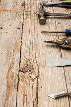 Tools lined up on a rustic wooden table.