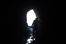 Silhouette of a person walking through a cave entrance toward the light.