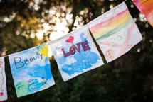 Children's paintings on fabric strung outside on a rope.