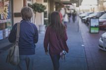 Two woman walking down the sidewalk