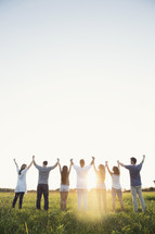 group of young adults standing with raised hands outdoors