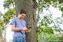 A young man standing next to a tree texting on his cellphone.