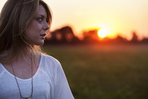side profile of a young woman standing outdoors at sunset