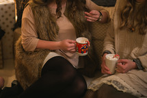 Two women sit and talk together while drinking hot chocolate.