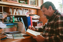a man sitting at his desk reading a Bible