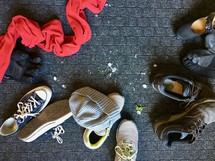 pile of shoes, scarves, beanies, and gloves on a floor