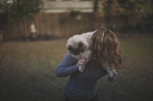 A blonde girl holding her cat behind her head