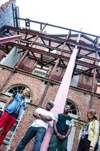 young adults standing in front of a brick warehouse